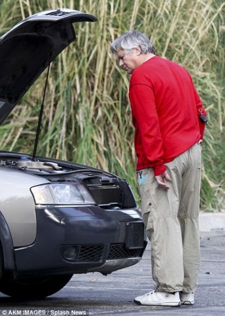 Richard Dean Anderson looks at his broken Audi.