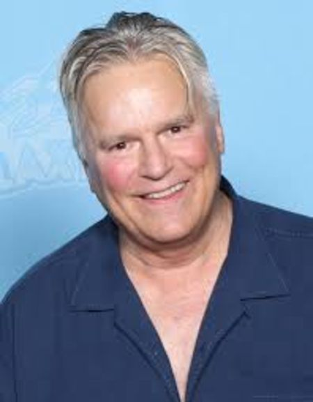 Richard Dean Anderson in a blue shirt poses for a picture.