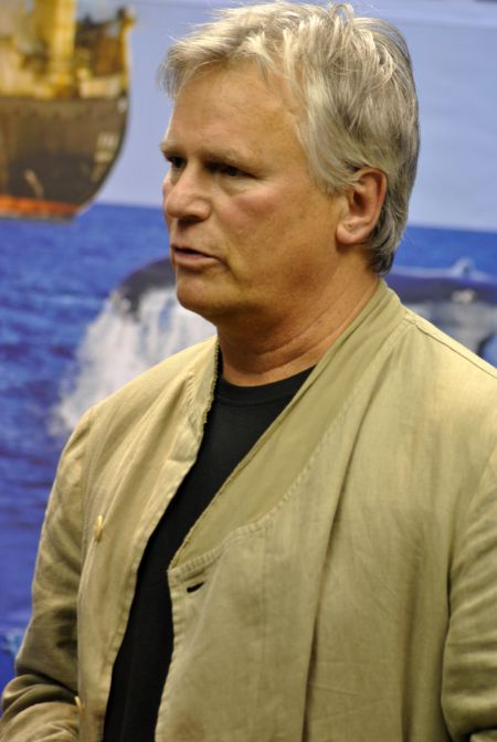 Richard Dean Anderson in a brown jacket poses for a picture.