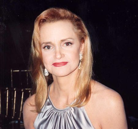 Swoosie Kurtz in a silver dress and brown hair poses for a picture.