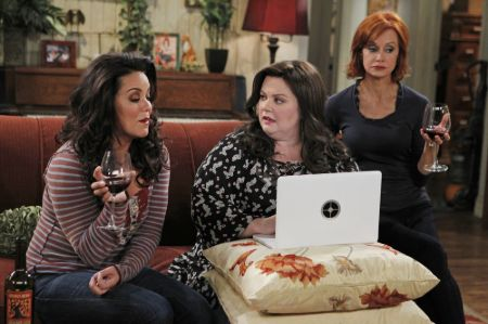 Swoosie Kurtz in a black top holding a wine class alongside the cast of Mike and Molly while shooting.