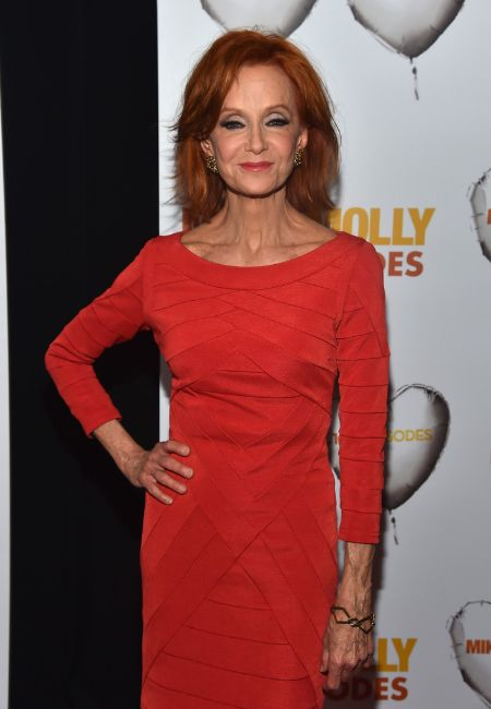 Swoosie Kurtz in a red dress poses at a public event.