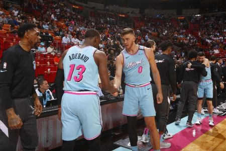 Meyers Leonard in the Miami jersey shaking hands with a teammate.