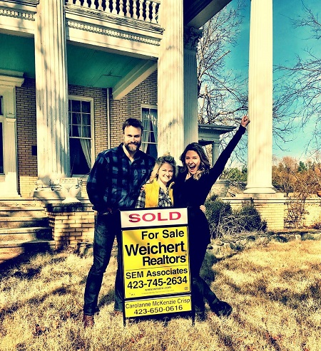 Jill Wagner and husband David Lemanowicz with the realtor in front of their house.