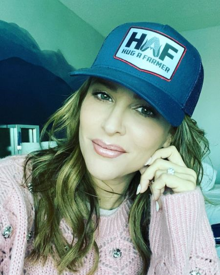 Jill Wagner in a pink sweater and blue cap poses for a picture,