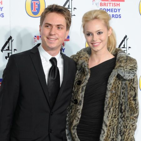 joe in a black suit, hannah wearing a black dress with a leopard print coat on the red carpet