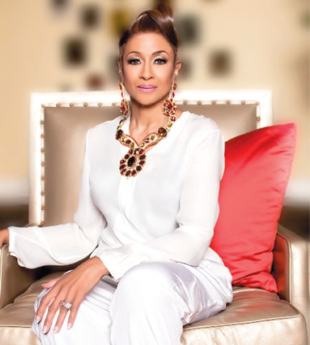 Dorinda Clark-Cole in a white top poses for a picture.