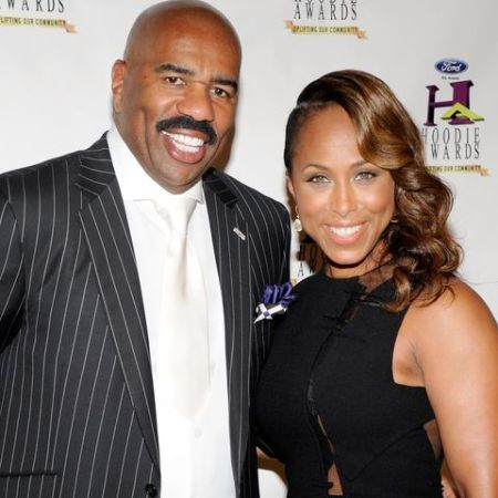 Steve Harvey in a black coat poses a picture with wife Marjorie Bridges-Wood.