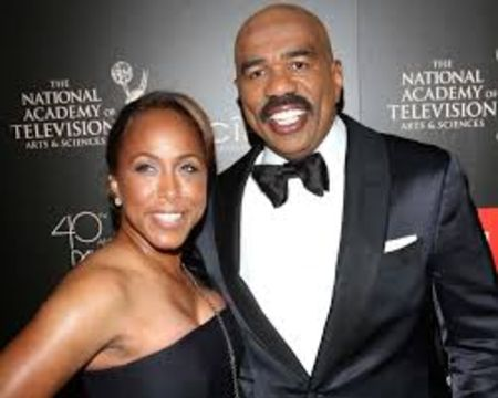 Steve Harvey in a black tux poses a picture with wife Marjorie Bridges-Wood at an award show.