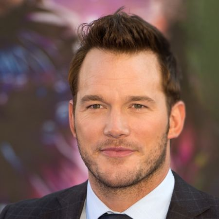 Chris Pratt in a black suit poses for a picture.