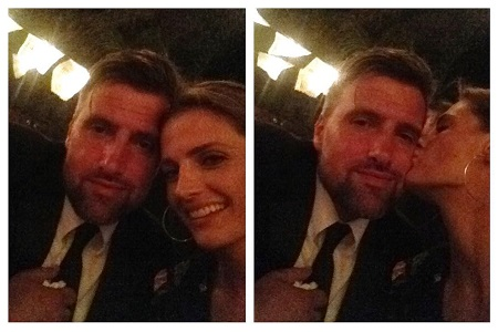 Stana Katic and husband Kris Brkljac being kissed by Stana on the chee.