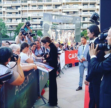 Stana Katic signing off autographs and husband Kris Brkljac behind her with the cameramen.