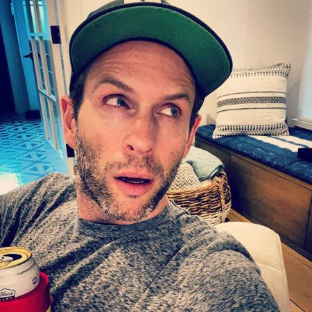 Actor Glenn Howerton in a grey t-shirt and a green cap at his home.