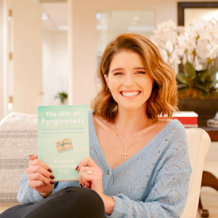 katherine in her home sitting on the couch, holding up her new book