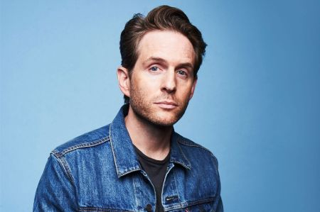 Actor Glenn Howerton in a blue jeans jacket poses for a picture.