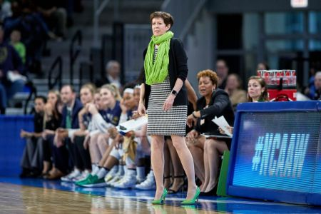 Coach Muffet McGraw in a black jacket and top at the sidelines coaching a game.
