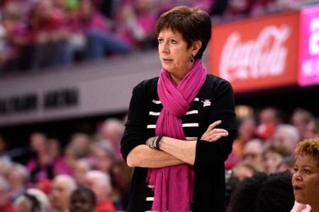 Muffet McGraw in a black sweater watches a match at the sidelines.