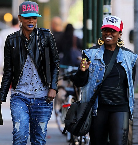 Missy Elliott and Sharaya J walking in the streets of New York with hats on.