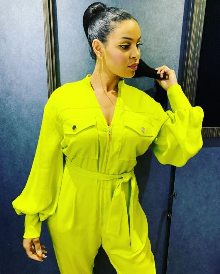 Jordin Sparks in a green-yellow dress poses for a picture.