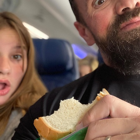 Ethan Suplee holding a sandwich and his daughter gasping beside him in an airplane. Both their faces are not complete.