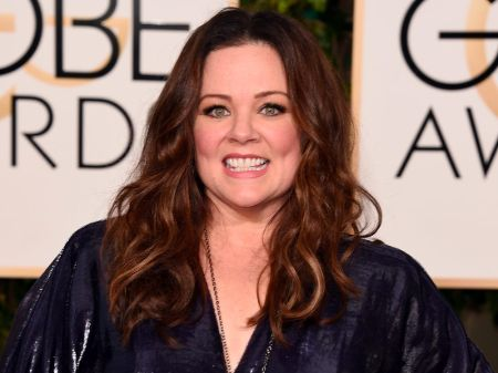 Melissa McCarthy in a black dress poses at an award show.