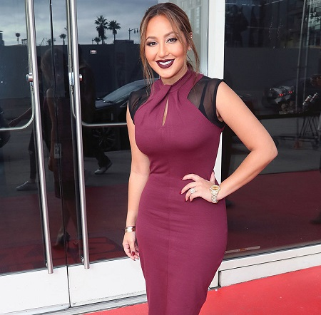 Adrienne Bailon in a stunning liver-colored skin-tight dress.