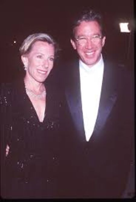 Laura Deibel in a black dress with Tim Allen at a party.