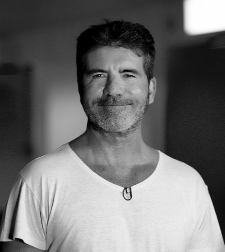 Simon Cowell in a white t-shirt poses for a picture.