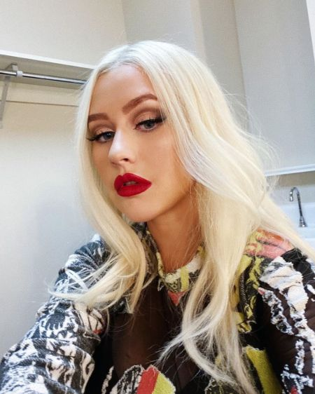 Christina Aguilera in a black top poses for a picture.
