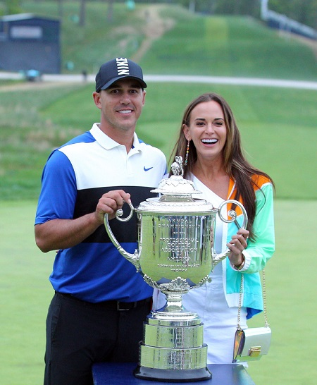 Brooks Koepka and his girlfriend Jena Sims pose with the Wanamaker Trophy after he won the PGA Championship golf tournament at Bethpage State Park, Bethpage, US, May 19, 2019.