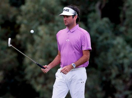 Bubba Watson in a pink t-shirt caught at the camera on a golf-court.