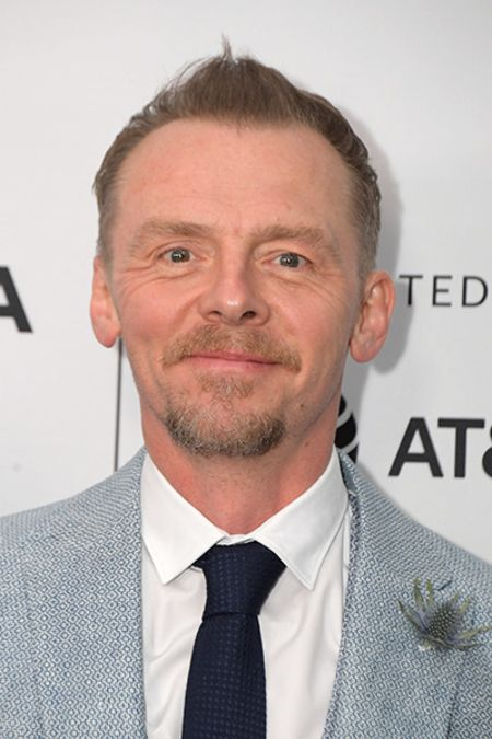 Simon Pegg in a grey suit poses for a picture.