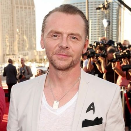 Simon Pegg in a white t-shirt and coat poses at a high-profile event.