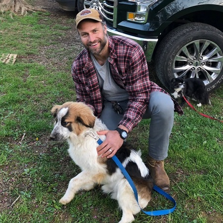 Jill Wagner's husband David Lemanowicz with a dog smiling at the camera.