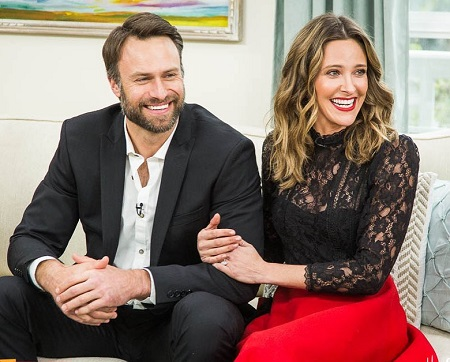 Jill Wagner with her arms through husband David Lemanowicz's left arm as they smile looking away from the camera.
