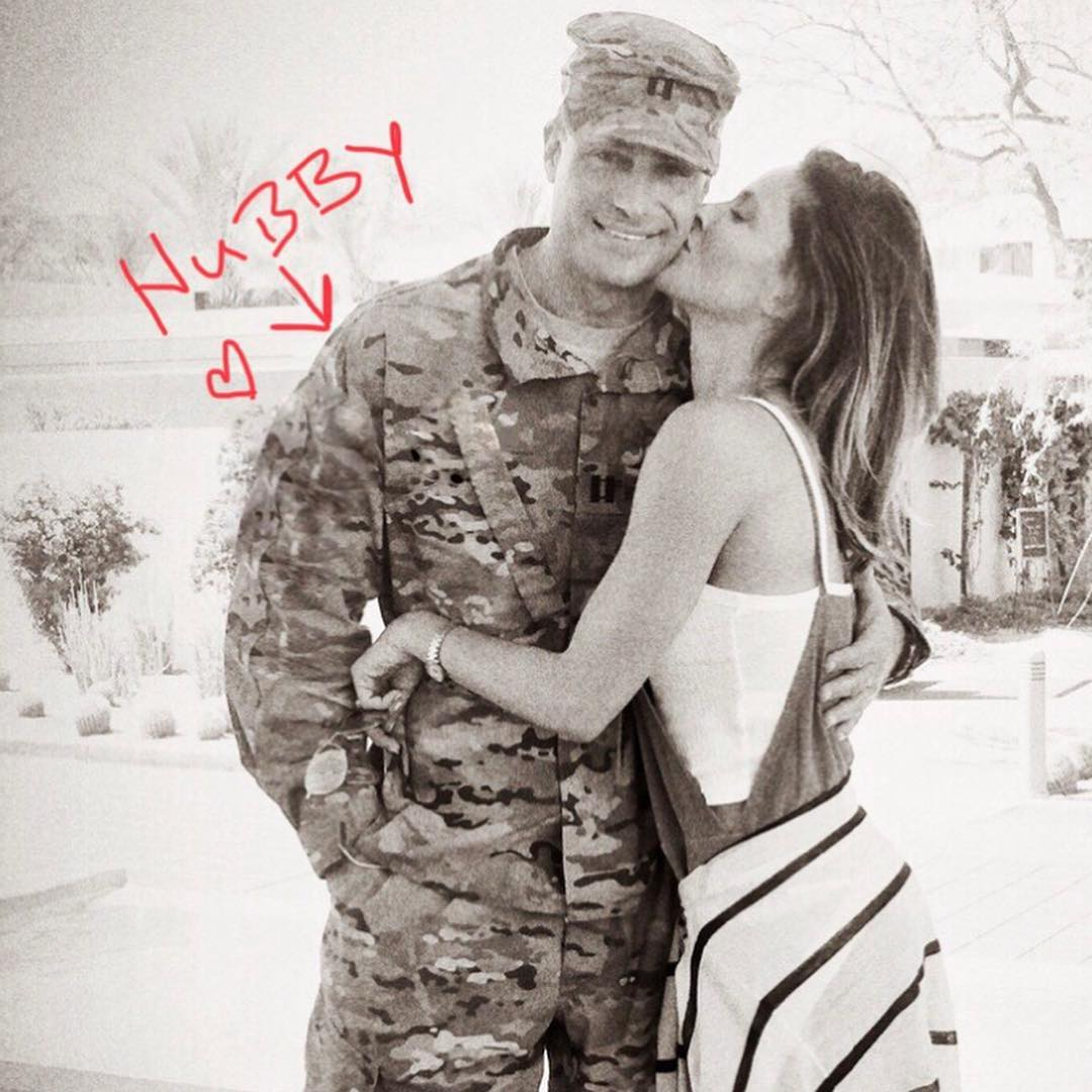 Jill Wagner kissing husband David on the cheek with him wearing an army outfit.