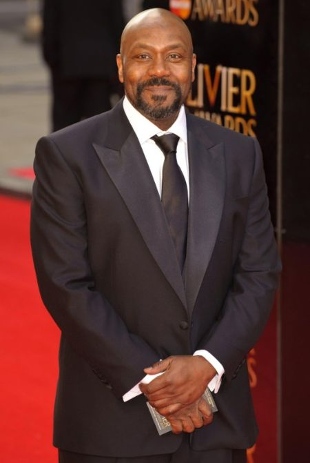 Lenny Henry in a black suit and black tie poses for a picture.