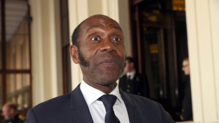 Lenny Henry in a black suit caught at the camera.
