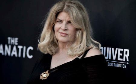 Kirstie Alley in a black dress poses at a movie premiere.