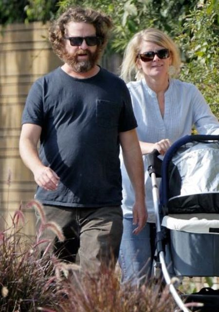 Quinn Lundberg in a white shirt poses a picture with husband Zach Galifianakis in a stroller.