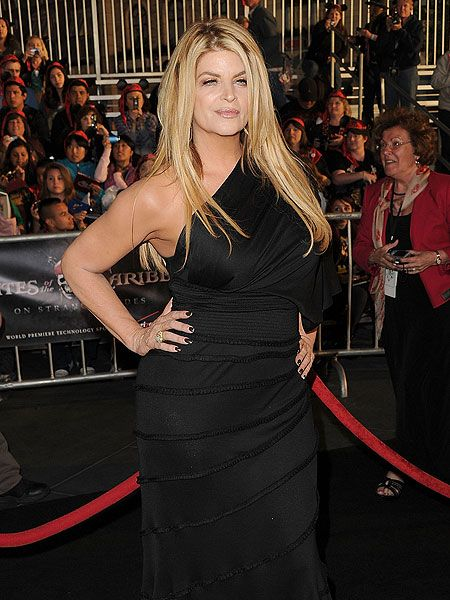 Kirstie Alley in a black dress poses for a picture.