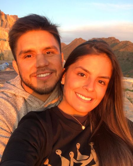 Henry Cejudo in a grey hoodie poses a picture with girlfriend Amanda Dallago Chaves.