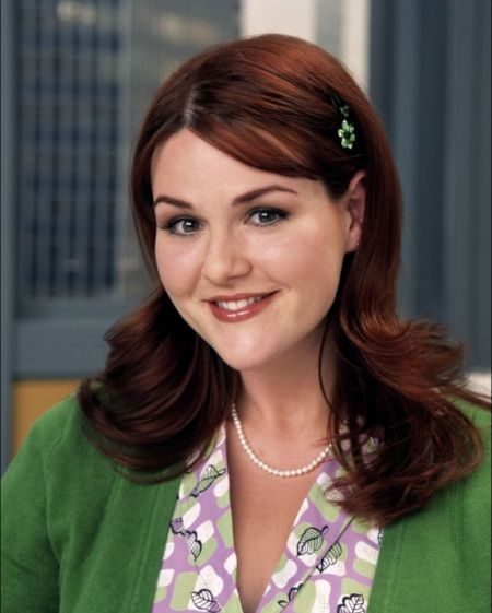Sara Rue in a green top poses for a picture.