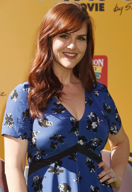 Sara Rue in a blue dress poses for a picture.