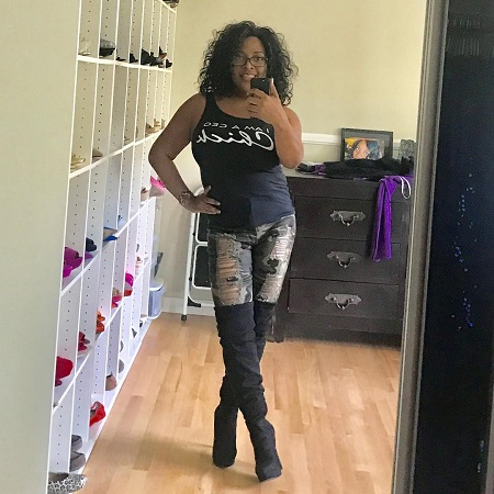 Sherri Shepherd taking a selfie in her closet in black top and ripped jeans.