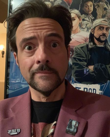 Actor Kevin Smith in a red coat poses for a picture in front of his poster.