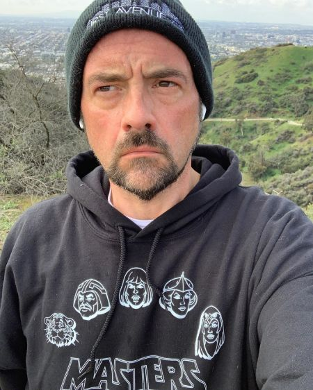 Filmmaker Kevin Smith in a blue hoodie poses for a picture.