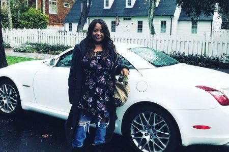 Sherri Shepherd poses for a picture in front of her car.