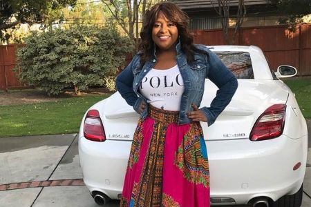 Sherri Shepherd in a blue jeans jacket poses in front of her Lexus.