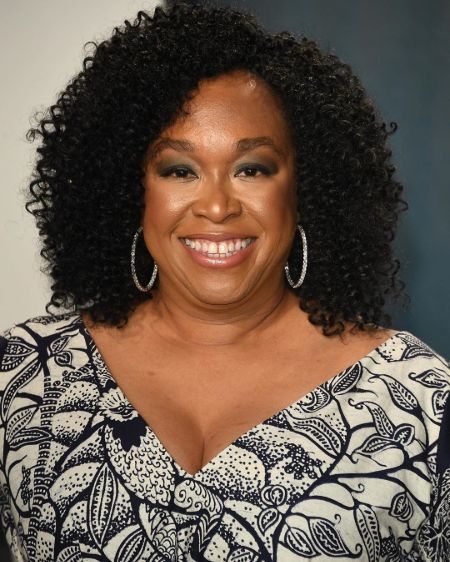 Shonda Rhimes in a black and white dress poses for a picture.